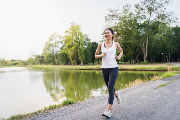 Здоровая красивая молодая азиатская женщина бегуна в спортивной одежде, бег и бег трусцой