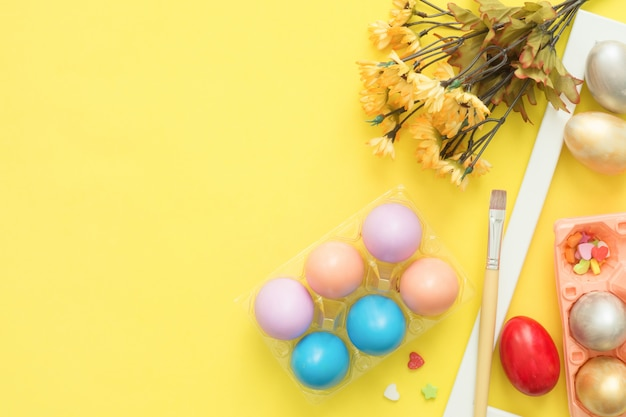 パステルカラーの組成と春の花で描かれたフラットレイアウト平面図カラフルなイースターエッグ