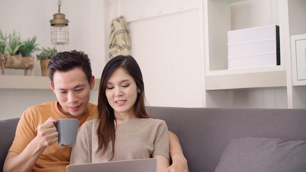 アジアカップルのラップトップを使用して、自宅の居間で暖かい一杯のコーヒーを飲む、甘いカップルを楽しむ