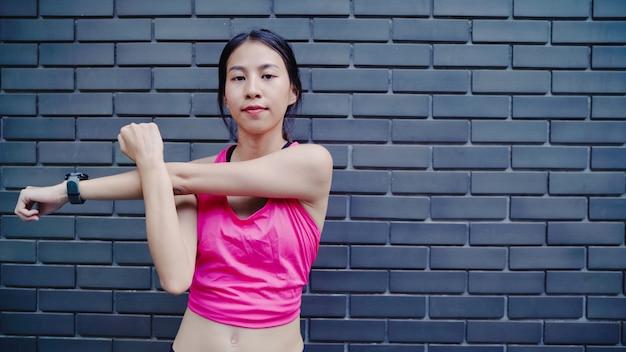 スポーツウェアの足の健康的な美しい若いアジアアスリート女性彼女の腕を温めとストレッチ