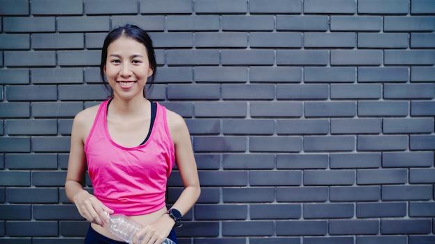 健康的な美しい若いアジアランナー女性が水を飲むので路上を走った後に疲れを感じる