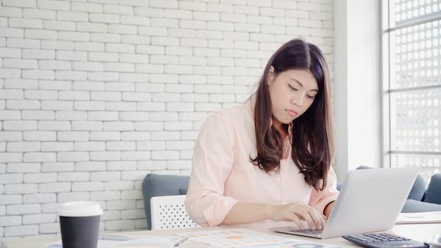美しい若い笑顔アジア女性自宅のリビングルームの机の上のノートパソコンで作業します。