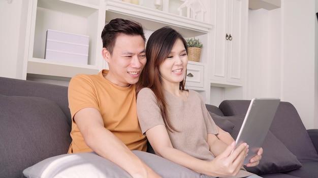 タブレットを使用してアジアカップルビデオ自宅の居間で友人と電話します。