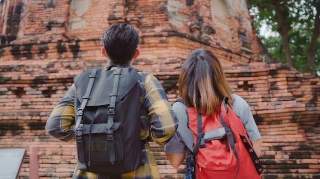 タイのアユタヤで休日の旅行を過ごす旅行者アジアカップル、バックパッカーの甘いカップルは伝統的な街の素晴らしいランドマークで彼らの旅を楽しみます。