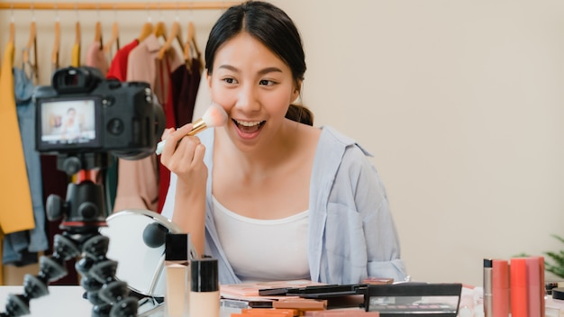 美しさのブロガーは、ビデオを録画するために正面のカメラに座っている美しさ化粧品を提示します。