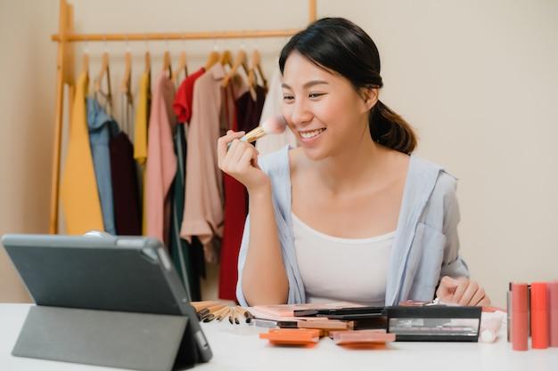 美しさのブロガーは、ビデオを録画するためにフロントタブレットに座っている美容化粧品を提示します。