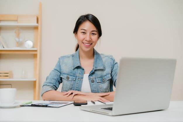 Компьтер-книжка красивой молодой усмехаясь азиатской женщины работая на столе в живущей комнате дома.