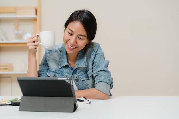 Молодая азиатская женщина работая используя таблетку проверяя социальные средства массовой информации и выпивая кофе пока ослабьте на столе в живущей комнате дома.