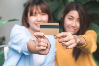 カフェレストランでタブレットコンピュータでクレジットカードを使用してアジアの女性オンラインショッピング
