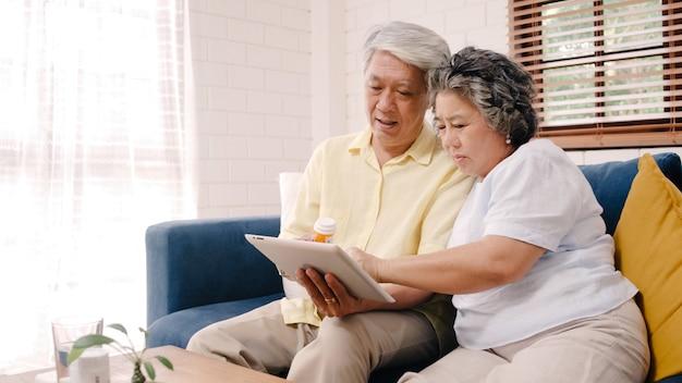タブレットを使用してアジアの高齢者夫婦はリビングルームで薬情報を検索し、自宅でリラックスしたときソファの上に横たわっている間一緒に時間を使用して夫婦。