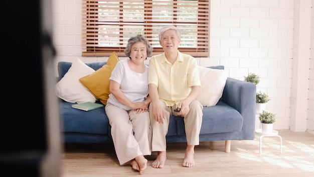 自宅でリビングルームでテレビを見ているアジアの老夫婦、自宅でリラックスしたときに甘いカップルはソファーに横たわっている間愛の瞬間を楽しんでいます。