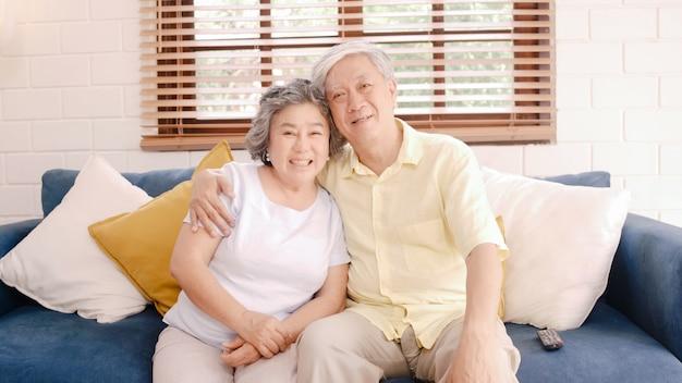 Азиатские пожилые пары смотря телевидение в живущей комнате дома, сладостные пары наслаждаются моментом влюбленности пока лежащ на софе когда расслаблено дома.