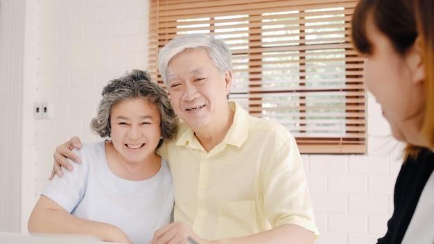 アジアのスマート女性エージェントは、文書、タブレット、ラップトップによって、老夫婦のための健康保険を提供しています。