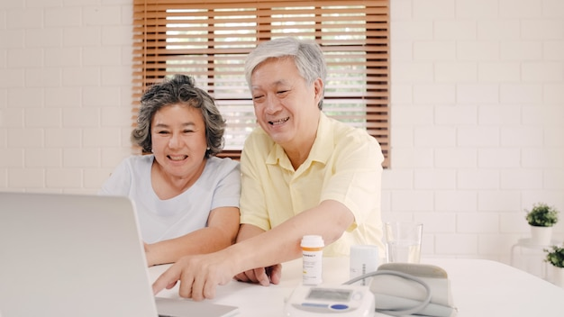 アジアの老夫婦の居間で医学情報についての医者とのラップトップ会議を使用して、自宅のソファーに横たわっている間一緒に時間を使用してのカップル。
