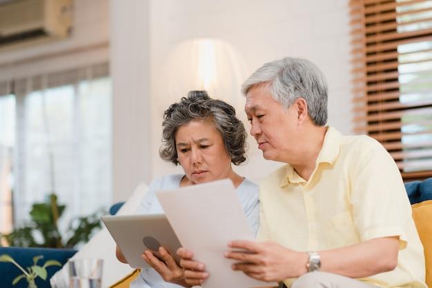 Азиатские пожилые пары используя таблетку смотря тв в живущей комнате дома, пары наслаждаются моментом влюбленности пока лежащ на софе когда расслаблено дома.