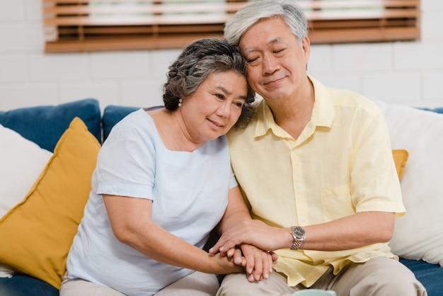 アジアの老夫婦が居間で一緒に服用しながら手を取り合って、幸せな気分を共有し、自宅のソファーに横になってお互いを支え合っています。