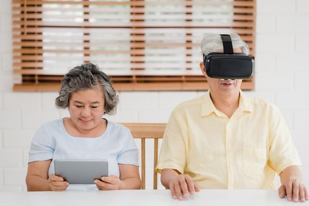 タブレットと仮想現実シミュレータを使用してリビングルームでゲームをしているアジアの老夫婦