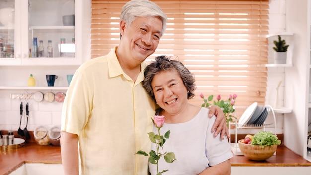 アジアの老夫婦が幸せな笑顔と花を持って自宅のキッチンでリラックスしながらカメラを探しています。