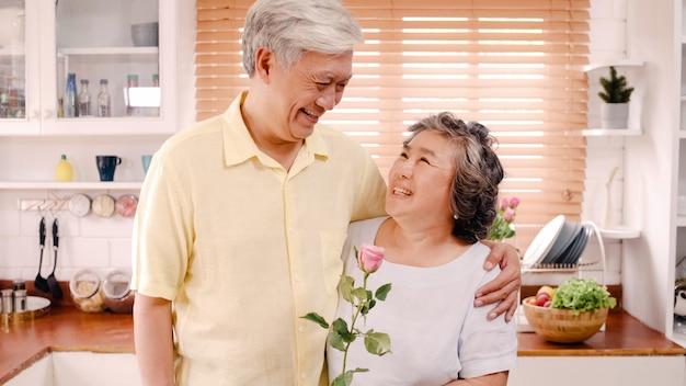 アジアの老夫婦が幸せな笑顔と花を持って自宅のキッチンでリラックスしながらカメラを探しています。ライフスタイルシニア家族は家のコンセプトで時間を楽しんでいます。カメラ目線の肖像画。