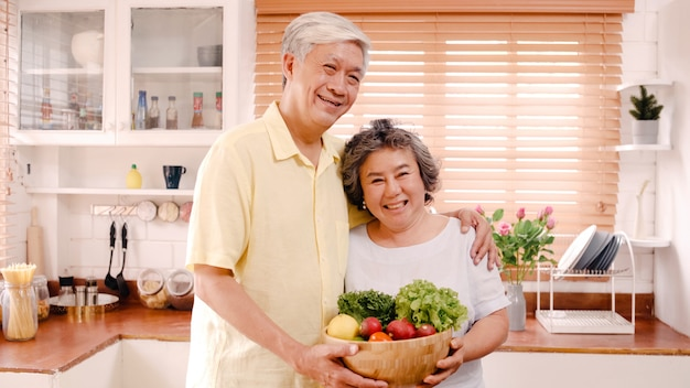 アジアの老夫婦が幸せな笑顔と果物を持って、自宅の台所でリラックスしながらカメラ目線を感じています。ライフスタイルシニア家族は家のコンセプトで時間を楽しんでいます。