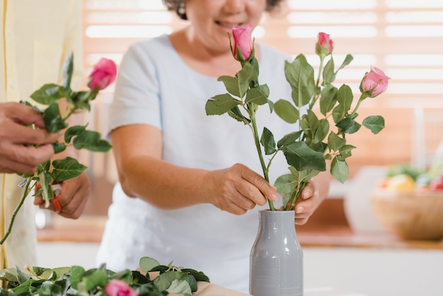 アジアの老夫婦が自宅の台所で木製のテーブルの上に花束の花を作る。