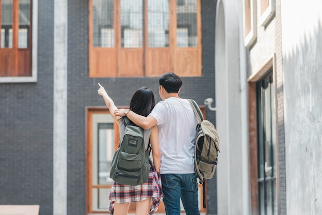 Пары путешественника азиата путешественника чувствуя счастливое путешествовать в пекине, китае, жизнерадостной молодой паре подростка гуляя на чайна-таун.