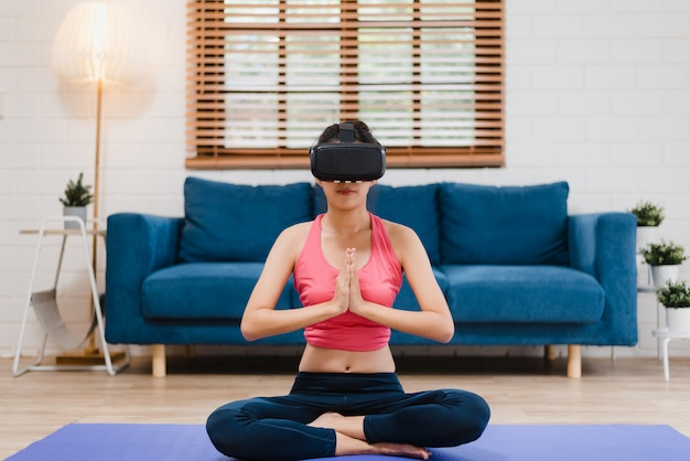 Молодая азиатская женщина подростка используя симулятор виртуальной реальности пока практикующ йогу в живущей комнате