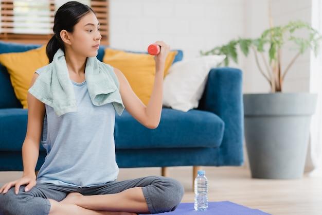 Йога молодой азиатской женщины практикуя в живущей комнате.