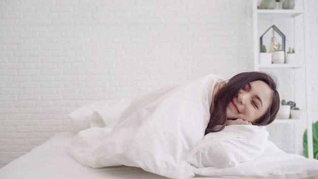 幸せな美しいアジアの女性は目を覚ます、笑みを浮かべて、寝室の彼女のベッドで彼女の腕を伸ばします。