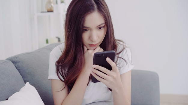 彼女のリビングルームのソファに横たわっている間スマートフォンを使用して美しいアジアの女性。