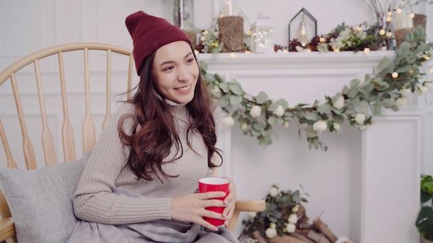 椅子に横たわっている間コーヒーまたは紅茶の暖かいカップを保持している美しい魅力的なアジア女性