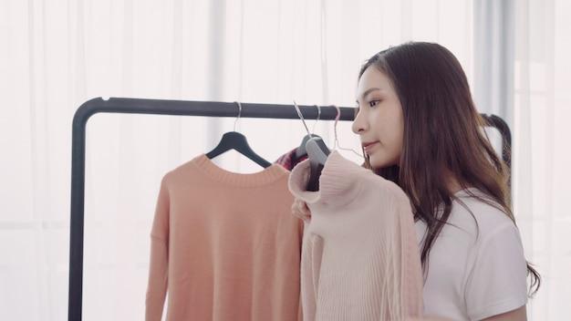 Домашний гардероб или магазин одежды, раздевалка. азиатская молодая женщина, выбирая ее мода наряд одежды