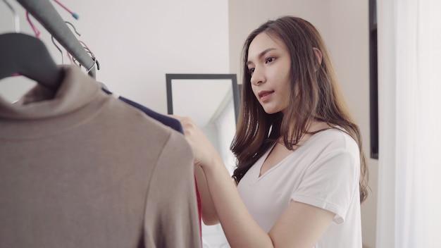 自宅のワードローブまたは衣料品店の更衣室。アジアの若い女性が彼女のファッション衣装服を選ぶ