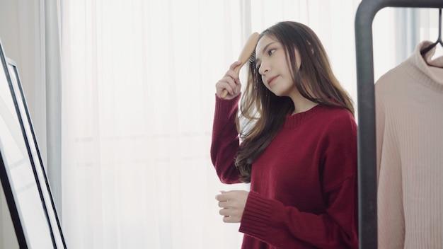 Портрет красивой привлекательной азиатской женщины расчесывая волосы и выбирая одежду в ее уборной дома.