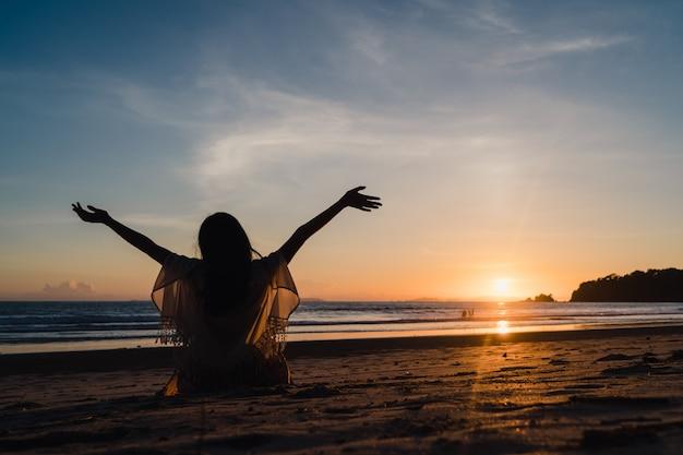 Молодая азиатская женщина наблюдая заход солнца около пляжа, красивое женское счастливое ослабляет наслаждается моментом когда заход солнца в вечере.