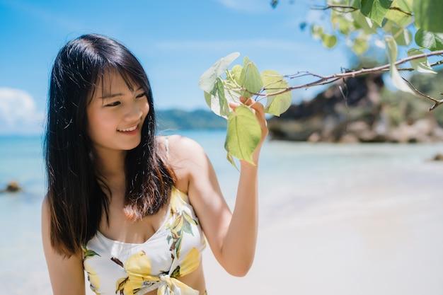 アジアの美しい若い女性は幸せ海の近くのビーチの上を歩いてリラックスします。