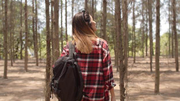 アジアのハイカーの女性が森でのトレッキング。