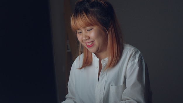 Молодая азиатская женщина работая поздно используя настольный компьютер на столе в живущей комнате дома.