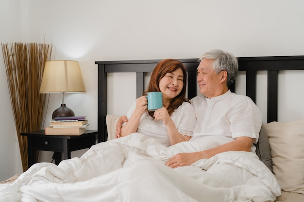 自宅のベッドで話しているアジアシニアカップル。アジアのシニア中国の祖父母、夫と妻の幸せは、朝のコンセプトで自宅の寝室のベッドに横たわっている間目を覚ます後コーヒーを飲みます。