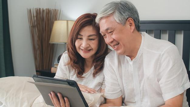自宅でタブレットを使用してアジアシニアカップル。アジアのシニア中国の祖父母、朝のコンセプトで自宅の寝室のベッドに横たわっている間家族の孫の子供と話しているビデオ通話。