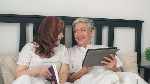 自宅でタブレットを使用してアジアシニアカップル。アジアのシニア中国の祖父母、夫は映画を見て、妻は朝のコンセプトで自宅の寝室のベッドに横たわって、目を覚ました後本を読みます。