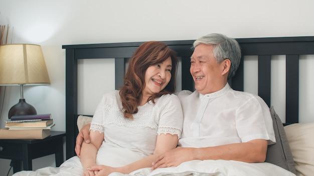 自宅のベッドで話しているアジアシニアカップル。アジアのシニア中国人の祖父母、夫と妻の幸せは、朝のコンセプトで自宅の寝室のベッドに横たわっている間目を覚ます後一緒にリラックスします。