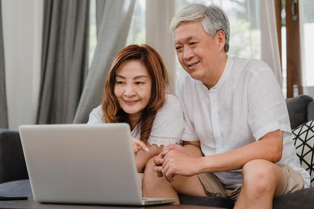 自宅でラップトップを使用してアジアシニアカップル。アジアのシニア中国人の祖父母は、インターネットをサーフィンして、ホームコンセプトのリビングルームのソファーに横たわっている間、ソーシャルメディアをチェックします。