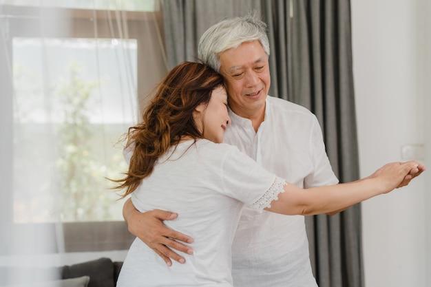 自宅のリビングルームで音楽を聴きながら一緒に踊るアジアの老夫婦、甘いカップルは、自宅でリラックスしたときに楽しみながら愛の瞬間を楽しみます。ライフスタイルのシニア家族は、ホームコンセプトでリラックスします。