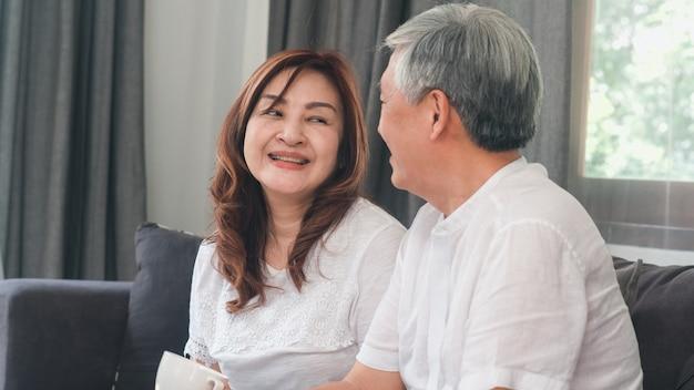 アジアの年配のカップルは自宅でリラックスします。アジアのシニア中国の祖父母、夫と妻の幸せな笑顔が自宅のコンセプトでリビングルームのソファに横たわっている間一緒に話して抱擁します。