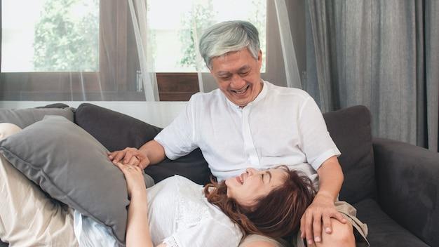 アジアの年配のカップルは自宅でリラックスします。アジアのシニア中国の祖父母、夫の幸せな笑顔の抱擁は、ホームコンセプトのリビングルームのソファーに横たわっている間彼女の妻の膝を横になります。