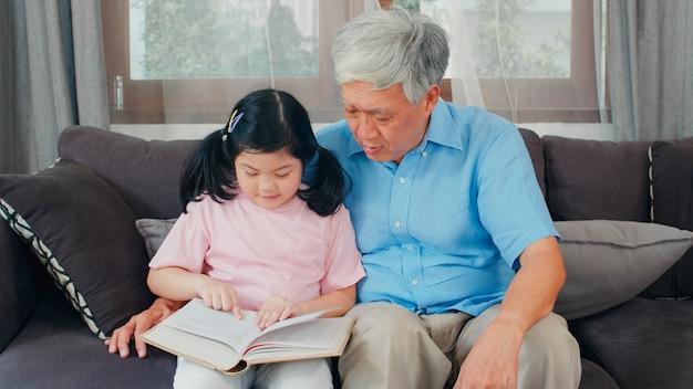 アジアの祖父は家でくつろいでいます。シニア中国人、幸せなおじいちゃんと若い孫娘の女の子は本を読んで楽しんで、リビングルームのコンセプトで一緒に宿題をします。