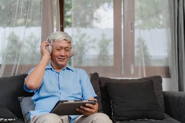 アジアの年配の男性は自宅でリラックスします。ホームコンセプトのリビングルームのソファに横たわっている間、タブレットのリスニングポッドキャストを使用してアジアの古い男性の幸せな着用ヘッドフォン。