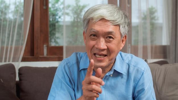 自宅でアジアの年配の男性のビデオ通話。ホームコンセプトのリビングルームのソファに横たわっている間家族の孫の子供と話している携帯電話のビデオ通話を使用してアジアのシニアの古い中国人男性。