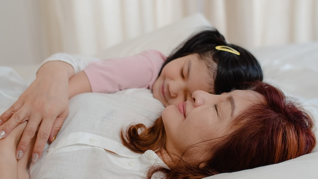 アジアの祖母は家で寝ています。シニア中国人、おばあちゃんは、夜のコンセプトで自宅の寝室のベッドに横になって目を覚ますための頬にキス若い孫娘の女の子とリラックスします。